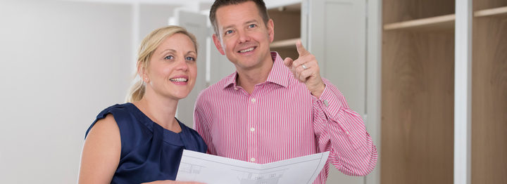 Mature Couple Looking At Plans For New Luxury Kitchen
